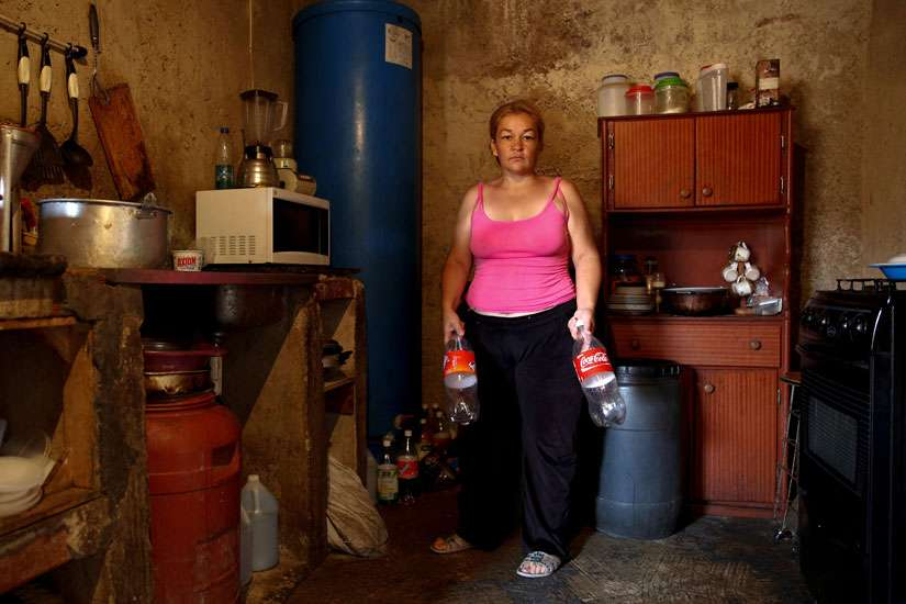 Yunni Perez holds plastic bottles used to carry water while she poses for a photo inside her home in a Caracas slum.