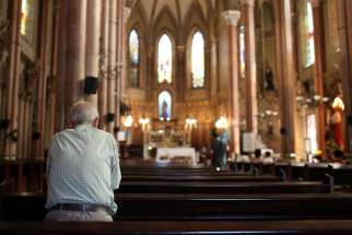 A man prays in 2013 at a church in Rio de Janeiro. Due to the swine flu outbreak in several parts of Brazil, parishes all over the country have adopted changes in liturgical practices.