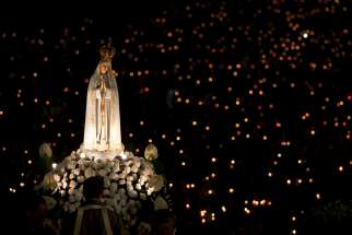 A statue of Mary is carried through the crowd in 2013 at the Marian shrine of Fatima in central Portugal. May 13 will mark the 100th anniversary of the first appearance of Our Lady of Fatima in Portugal.