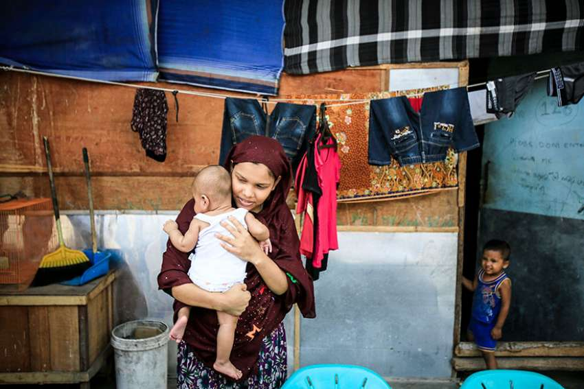 A Rohingya woman holds her 2-month-old baby in early February at a refugee shelter in Medan, Indonesia. The woman and her husband fled persecution in their village in Myanmar and have been waiting for two years to be resettled to Malaysia or Australia.
