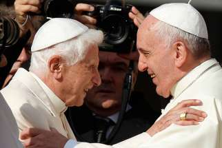 Pope Francis greets emeritus Pope Benedict XVI during an encounter for the elderly in St. Peter's Square at the Vatican Sept. 28.