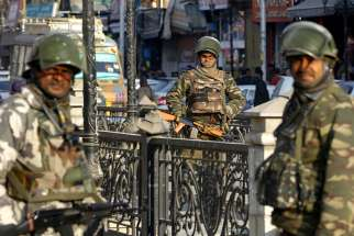 Indian paramilitary soldiers stand guard Jan. 22 in Srinagar, near the India-Pakistan border. More than 40,000 villagers have fled their homes since Indian and Pakistani soldiers began exchanging fire across their borders.