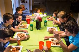 "A large family is pictured eating dinner together in late May at their St. Louis home. A family that chooses to watch TV or play with their smartphones rather than talk at the dinner table is ""hardly a family,"" Pope Francis said."
