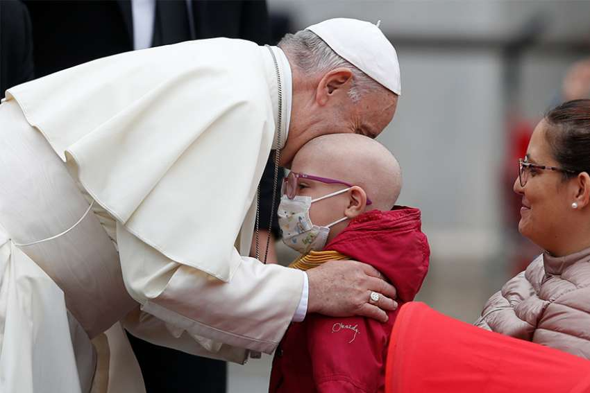 Pope Francis embraces a sick boy during his general audience in St. Peter's Square at the Vatican Oct. 17.