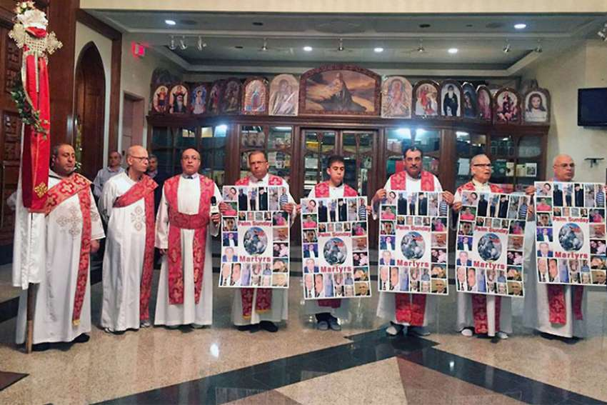 Coptic clergy hold signs to remember victims of the Palm Sunday attack in Egypt during a service at the Church of Virgin Mary and St. Athanasius on April 18, 2017, in Mississauga, Ontario.