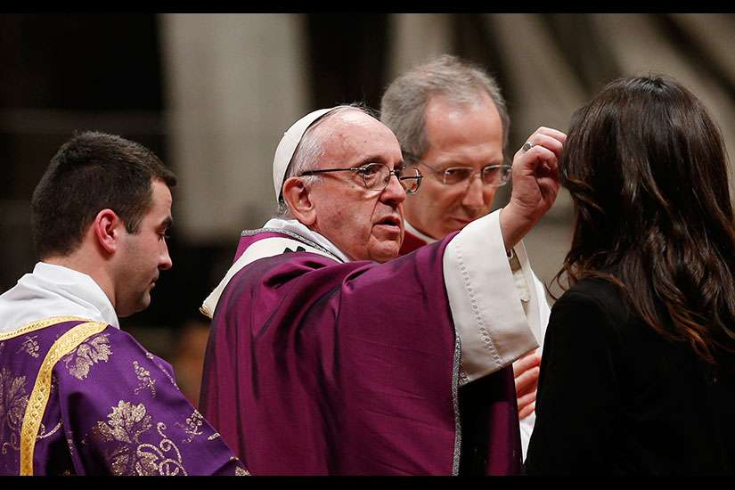 Pope Francis gives ashes to a woman as he celebrates Ash Wednesday Mass in St. Peter's Basilica at the Vatican Feb. 10.