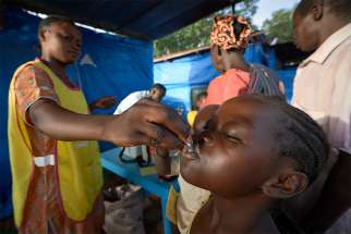 A child swallows an oral cholera vaccine at a displaced persons camp at the Holy Family Catholic Church in Wau, South Sudan, April 17.