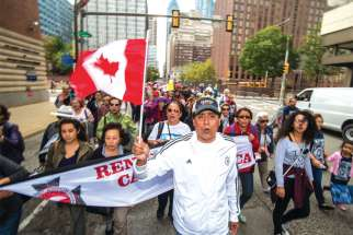 Members of the Charismatic Renewal movement from the Greater Toronto Area fly the Canadian flag in downtown Philadelphia on their way to Mass with Pope Francis on Sept. 27.