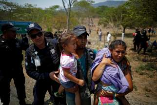 A family of Central American migrants is detained by Mexican federal police officers April 22, 2019, in Pijijiapan, Mexico, during their journey toward the United States.