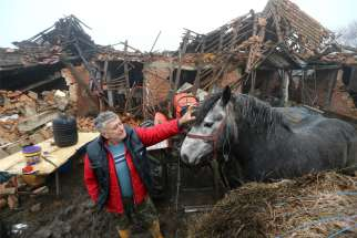Farmer Tomislav Suknaic touches his horse in front of his destroyed home in the village of Majske Poljane, Croatia, Dec. 30, 2020, following an earthquake. Pope Francis offered condolences and prayers for the victims of the magnitude 6.4 earthquake that rocked central Croatia the previous day, killing at least seven people and injuring dozens.