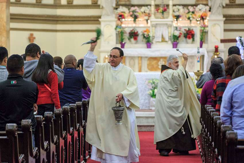 "Father Todd Carpenter and Deacon Angel Rivera bless the congregation with holy water during the Easter Vigil in 2016 at St. Paul Church in Wilmington, Del. The Roman Missal, which spells out specifics of how the vigil is to be celebrated, describes it as the ""mother of all vigils."""