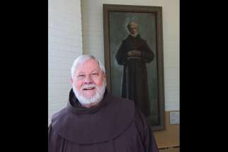 Fr. Roland Bonenfant, director of the Frédéric Jansoone Centre in Trois Rivieres, Que., stands in front of a painting of the Franciscan who was beatified by Pope John Paul II in 1988.