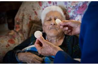 Pueblo Indian Sister Mary Rosita Shiosee brings Communion to Aurelia Synella in Laguna Pueblo in New Mexico, Oct. 30, 2014.