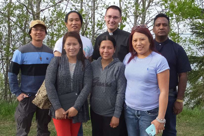 Catholics from St. John the Baptist Church who escaped the Fort McMurray wildfire in Alberta are pictured in Lac La Biche May 7. Back row from left are Leo Ganancial, Gary Agarin, Fathers Andrew Schoenberger and Prabhakar Kommareddy. Front row are Norie Sanchez, Shiela Ganancial and Cindy Julapton.