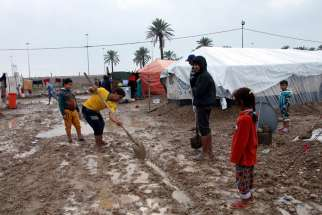 Young internally displaced Iraqis try to dig a drainage trench after heavy rains in early November at a camp in Baghdad.