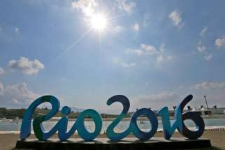 Canoe athletes preparing for the 2016 Summer Olympics paddle behind an Olympic sign Aug. 2 in Rio de Janeiro.