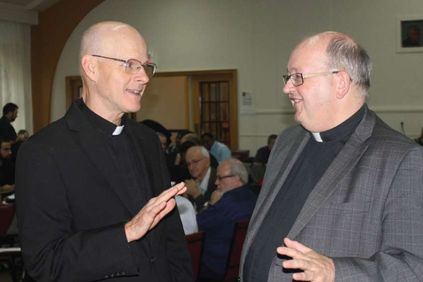Msgr. Stephen Rossetti, left, speaks with Fr. Raymond Lafontaine during an Oct. 26 day-long conference for Montreal priests.