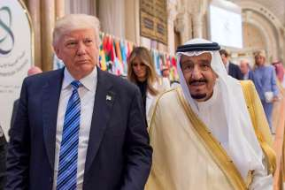 U.S. President Donald Trump walks with Saudi King Salman during the opening session of the Gulf Cooperation Council summit May 21 in Riyadh, Saudi Arabia.