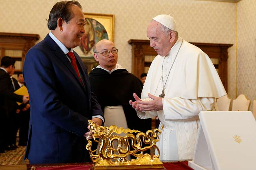 Pope Francis exchanges gifts with Truong How Binh, vice prime minister of Vietnam, during a private audience at the Vatican Oct. 20.
