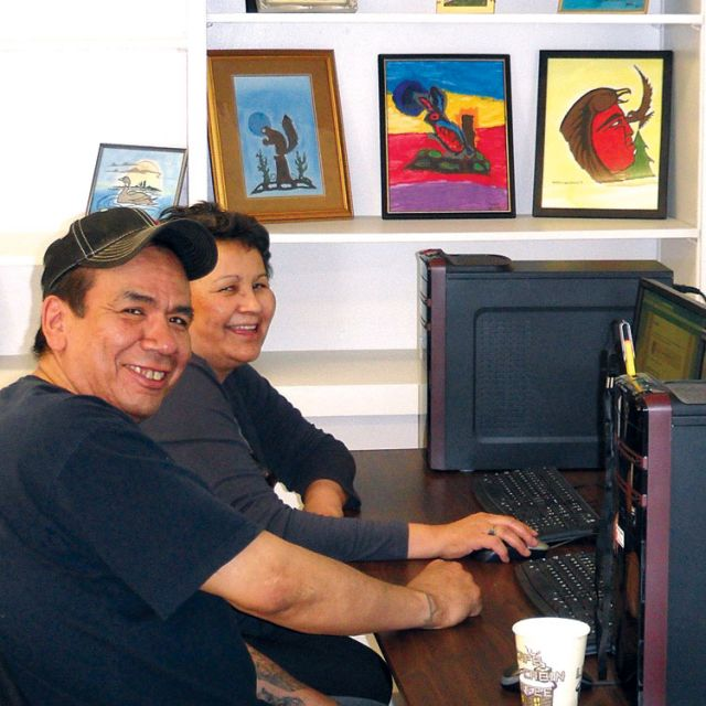 Two aboriginal students work side-by-side at computers inside the Apitisiwin Education Learning Centre in Cochrane, Ont.