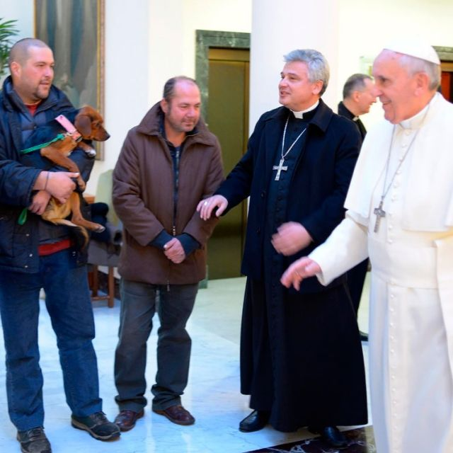 Pope Francis talks with three men Dec. 17 who live on the streets near the Vatican. As part of a low-key celebration of his 77th birthday, the pope celebrated morning Mass and had breakfast with the men.