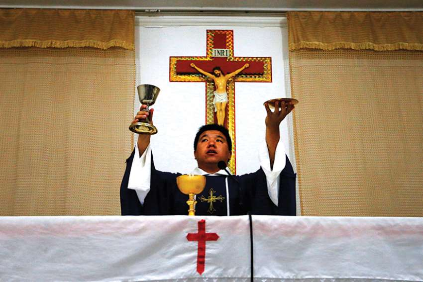 A priest celebrates Mass in 2012 in a makeshift chapel in a village near Beijing. For the first time in decades, all of the Catholic bishops in China are in full communion with the pope, the Vatican announced Sept. 22.