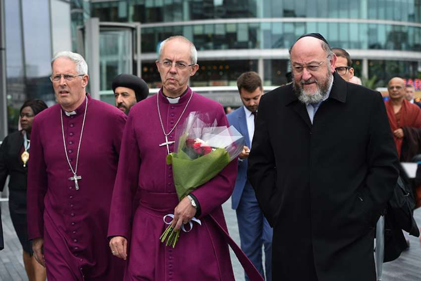 Anglican Archbishop Justin Welby of Canterbury, centre, attends a June 5 vigil with Chief Rabbi Ephraim Mirvis for the victims of the London Bridge terror attacks.