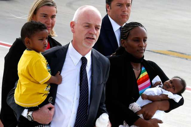 Meriam Ibrahim of Sudan carries one of her children as she arrives with Lapo Pistelli. She hopes to settle in New Hampshire.