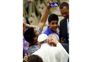 Archbishop Bernardito Auza said everyone wants to see the Pope because of the interest in the Laudato Si' encyclical. In this photo, a man makes a selfie as Pope Francis blesses a pilgrim during the pontiffs weekly audience in Paul VI hall at the Vatican Aug. 12.