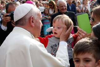 ope Francis greets a child during a gathering with young people in Piazza Vittorio in Turin, Italy, June 21.