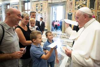 Pope Francis holds a paper airplane children gave him during a meeting at the Vatican Sept. 25, 2019, with members of the Emmanuel Community from Lecce, Italy, who are especially active in serving the poor, the disabled and marginalized. The pope told them they can fight off fatigue and discouragement by being with Christ as they work with so many people in difficulty.