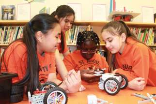 Keanna Tejado, Eunice Doronio, Chanel Ofosu and Patricia Barahona work on a robot. St. Andre's Robo Giants club is headed for Destination Imagination world finals.