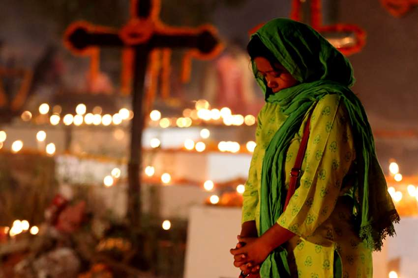 An Indian Christian woman prays Nov. 2, All Souls' Day, at a cemetery in Bhopal. A Catholic bishop has sought protection for the Christian community in the central Indian state of Madhya Pradesh after Hindu nationalists marched through the streets waving burning torches and denouncing missionaries.