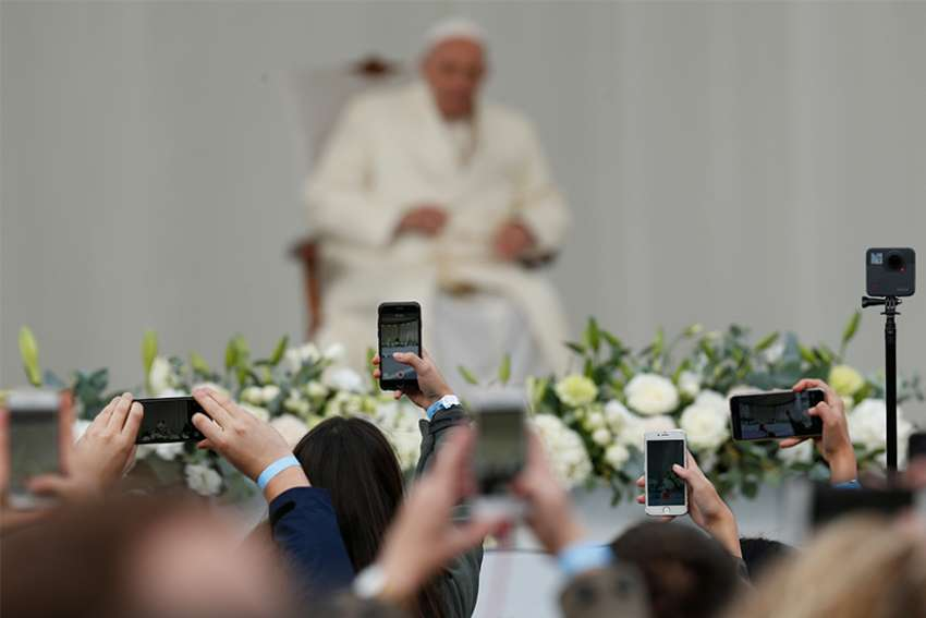 People use phones to capture images of Pope Francis as he leads a meeting with young people in the square adjacent to the cathedral in Vilnius, Lithuania, Sept. 22.
