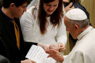 Pope Francis blesses the marriage certificate of a couple during his general audience in Paul VI hall at the Vatican Dec. 14, 2016.