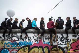 People sit on the East Side Gallery and watch a circus performance in Berlin Nov. 9. The president of the German bishops' conference praised Catholics who helped bring down the Berlin Wall, but also urged the church to look ahead to its future mission.