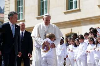 Pope Francis greets a child while meeting with Colombian President Juan Manuel Santos and other government authorities in the courtyard of the presidential palace in Bogota, Colombia, Sept. 7.