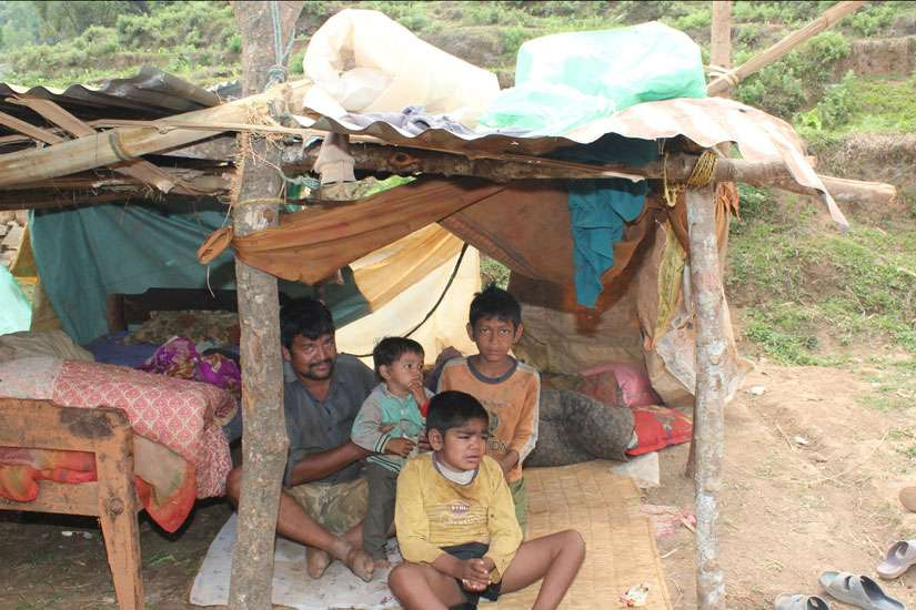 Subu Pariyar and his children sit inside a makeshift shelter May 9 on top of Baretol mountain in Nepal. Their home was destroyed in the magnitude-7.3 earthquake April 25.