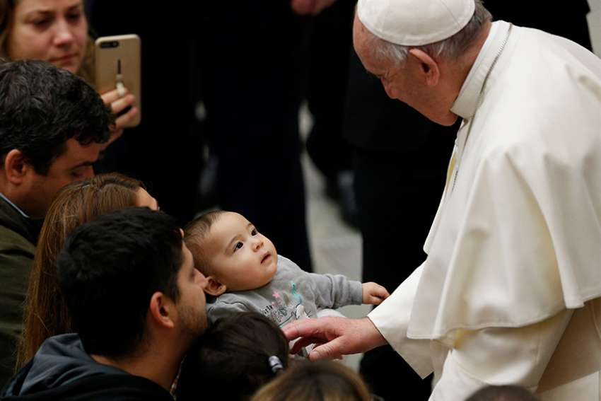 Pope Francis greets a baby during his general audience in Paul VI hall at the Vatican Jan. 9.