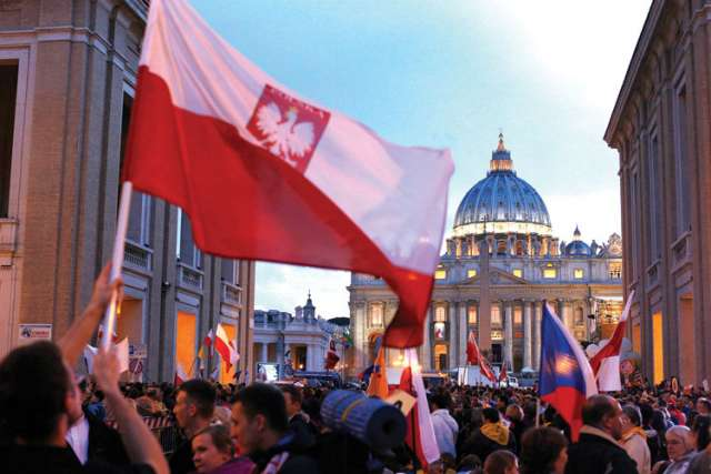 Poland's flag is seen as pilgrims wait on Via della Conciliazione outside St. Peter's Square at the Vatican April 26, the eve of the canonization of Sts. John XXIII and John Paul II.
