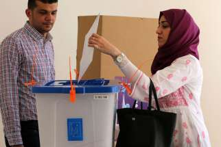 An Iraqi woman living in Jordan casts her ballot at a polling station in a government school in Amman April 27. Iraqi Catholic refugees, along with their exiled countrymen, are voting in the first parliamentary polls since the 2011 withdrawal of U.S. tro ops from their nation.