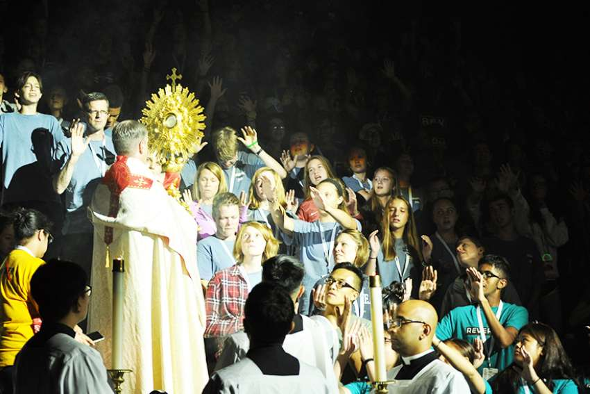 Fr. Christopher Martin carries the Holy Eucharist in the monstrance through the crowds during Saturday adoration at Steubenville Toronto.