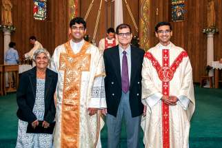 The Alemão brothers, Favin and Ryan, right, with their grandmother Crescencia Mergulhão Carvalho and father Felix at Favin's First Mass at St. Edward the Confessor on May 14.