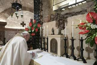 "Pope Francis signs his new encyclical, ""Fratelli Tutti, on Fraternity and Social Friendship"" after celebrating Mass at the Basilica of St. Francis in Assisi, Italy, Oct. 3, 2020."