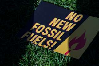 A sign protesting fossil fuels is seen on the lawn outside of the U.S. Capitol during a protest in Washington Oct. 18, 2019.