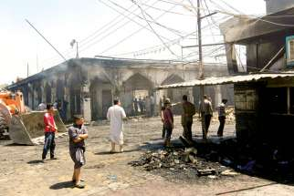 Iraqis inspect the scene of a July 8 suicide bomb attack outside Imam Mohammed shrine near Baghdad.