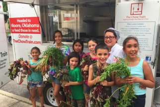 Joan Cheever poses with young farmers in front of the Chow Train food truck.