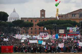 The dome of St. Peter's Basilica is seen in the distance as people attend the Family Day rally at the Circus Maximus in Rome Jan. 30. The rally was held to oppose a bill in the Italian Senate that would allow civil unions for homosexual and heterosexual couples.