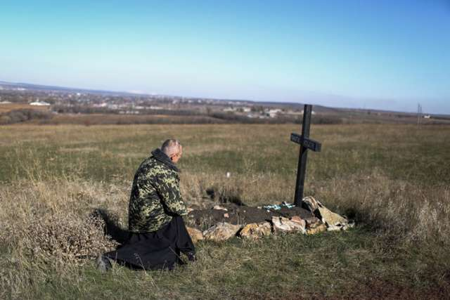 A priest kneels next to the grave of a soldier at a Ukrainian military camp near the eastern Ukrainian town Kramatorsk Oct. 26. Ukrainian President Petro Poroshenko claimed a landslide victory for pro-western parties Oct. 26 in the country's key parliamentary elections.