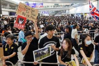 Anti-extradition bill protesters hold placards for arriving travelers during a protest at Hong Kong International Airport Aug. 9, 2019. More than 1,000 Catholics prayed during a candlelight vigil outside the Cathedral of the Immaculate Conception Aug. 8 for Hong Kong to solve its political crisis in a nonviolent manner.